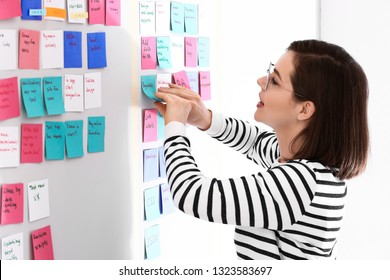 Young woman near scrum task board in office