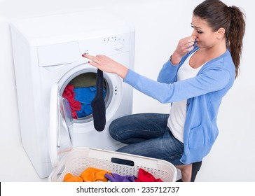 Young woman near the washing machine is keeping smelly sock.