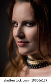 young woman with necklace looking at camera