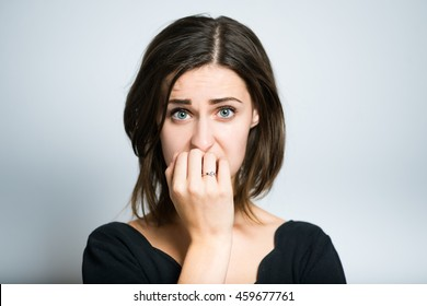 young woman nervous and bites nails, studio photo isolated on a gray background