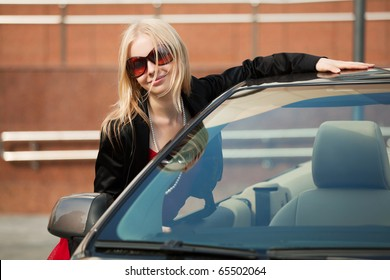 Young woman with a new convertible.