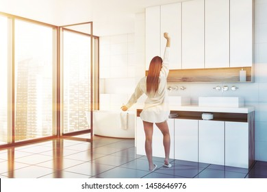 Young woman in nightgown standing in panoramic bathroom with white tile walls, comfortable white bathtub and double sink on white countertop. Toned image