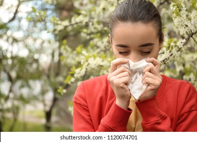 Young woman with nose wiper near blooming tree. Allergy concept