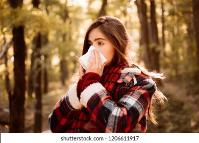 Young woman with nose wiper near autumn tree. Sick girl with runny nose and fever. Showing sick woman sneezing at autumn park. Young woman having flu and blowing her nose