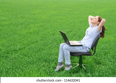 Young woman with notebook have rest on the grass