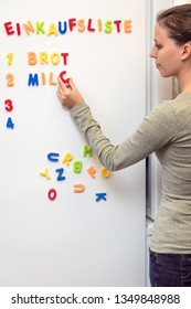 young woman notes the shopping list on the fridge with colorful magnet letters, german word Einkaufsliste which means shopping list