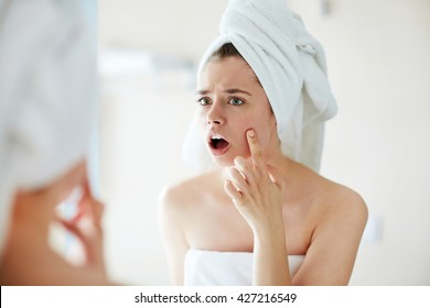 Young woman noticing a pimple on her face in terror