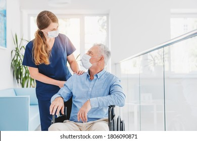 Young woman nurse explaining information to man patient in wheelchair in medical face mask while talking together in hospital. Epidemic and virus concept