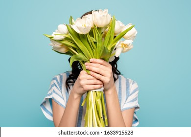 young woman obscuring face with bouquet of white tulips isolated on blue