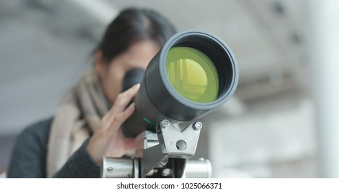 Young Woman observe through telescope