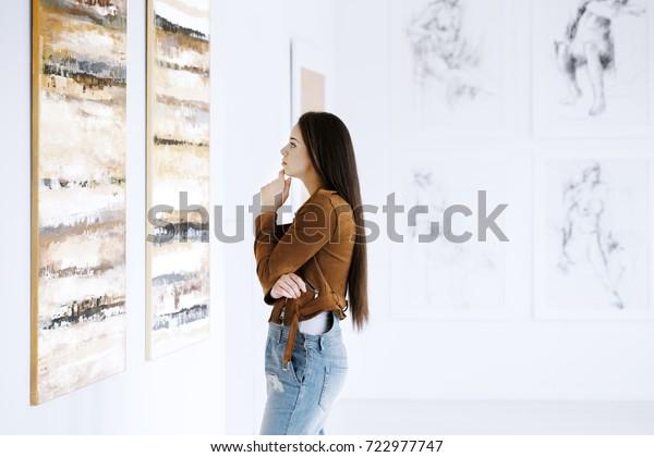 若い女性が、有名なアーティストコレクションを持つ美術館を訪れながら絵を観察する