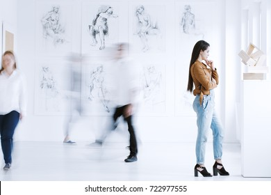 Young woman observing sculpture in modern art gallery with drawings. Art gallery concept