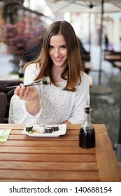 Young woman offering you sushi in a restaurant