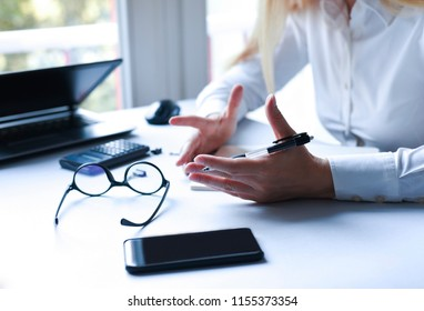 Young woman in office explaining. Hands close up gesticulating.