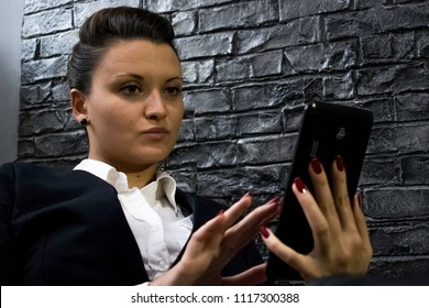 A young woman in the office holds a tablet in her hands