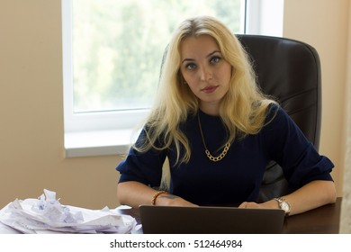 Young woman in the office with pile of documents