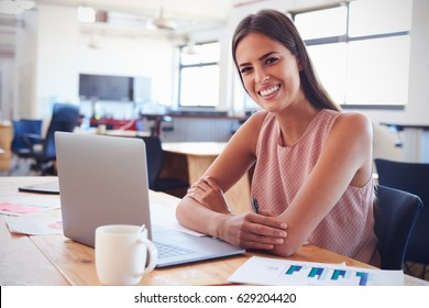 Young woman in office using laptop computer smiles to camera