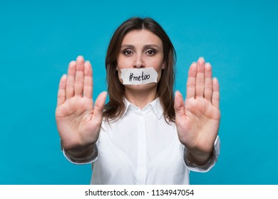 Young woman in an office white shirt with a mouth plastered with plaster and an inscription metoo, shows gesture with both hands of stop harassment and violence.  Hand stop no.