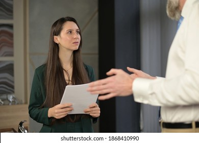 Young woman, office worker communicates with a senior very tall colleague, looks up at him