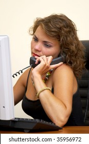 Young woman at the office workplace calling on phone