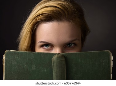 Young woman with old book on a dark background . On cover free space for your text .