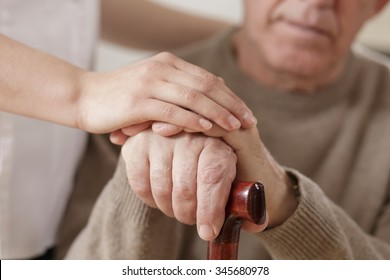 Young woman and old man holding hands