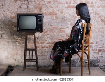 A young woman and an old television in front of a brick wall.