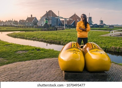 young woman at the Old wooden Windmills of the Zaanse Schans village with historical green wooden house`s during sunset at Spring