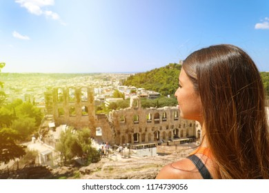 Young woman on the Acropolis of Athens, Greece. Tourist female looking to ancient theater and Athens landscape in a summer day on the Acropolis.