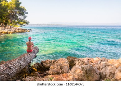 Young woman on a beach enjoying the view near Malinska on island Krk, Croatia. Travel adventure and freedom concept. Copy space female looking view of sea background.