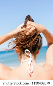Young woman on the beach holding her hair, soft focus