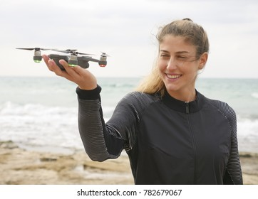 Young woman on the beach preparing to take off a drone in gesture mode from the palm of her hand