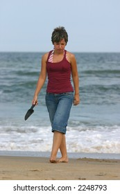 young woman on beach with shovel to dig for shells