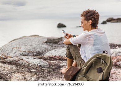young woman on the beach at sunset with mobile phone in hands