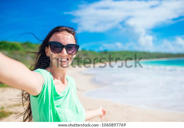 Young woman on the beach taking selfie