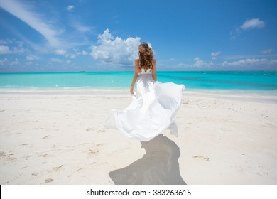 Young woman on the beach of tropical island in white dress.