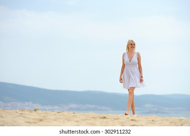 Young woman on the beach in white dress