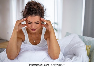 Young woman on bed, headache. Vertigo illness concept. Woman hands on his head felling headache dizzy sense of spinning dizziness,a problem with the inner ear, brain, or sensory nerve pathway.