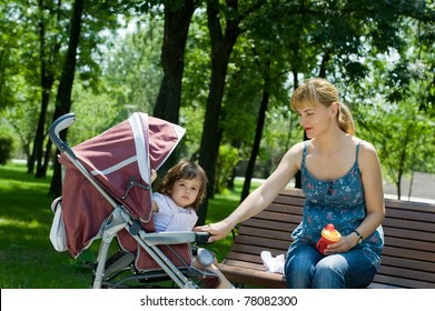 Young woman on bench with a pram in a park
