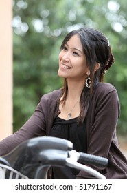Young woman on a bicycle outdoors smiling