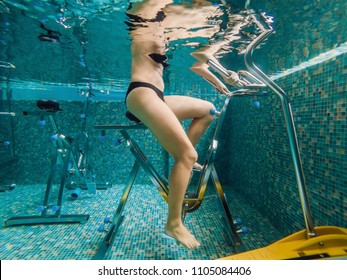 Young woman on bicycle simulator underwater in the pool.