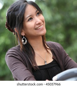 Young woman on a bicykle outdoors smiling