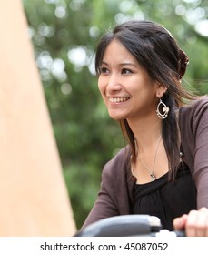 Young woman on a bike, smiling while outdoors