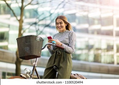 Young woman On Bike Using Mobile Phone
