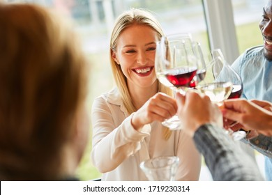 Young woman on a birthday party with friends while toasting with red wine