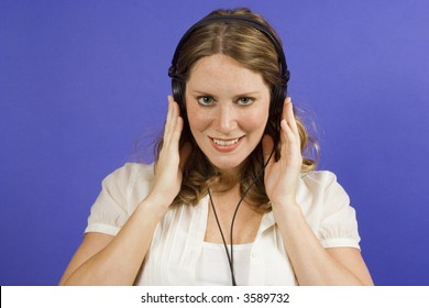 Young woman on blue listening to headphones