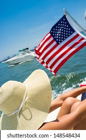 Young woman on a boat wearing a big hat with American flag waving and boat passing by.