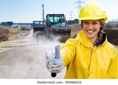 Young woman on a building site with thumb up