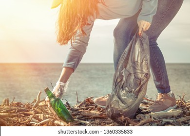 A young woman on a clean-up of the coastal area, collecting garbage. Sea and sky in the background. Earth day and ecology. Light.