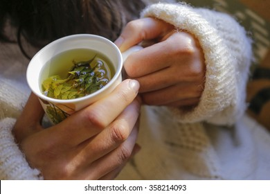 The young woman on the couch and with sage tea on the hand.